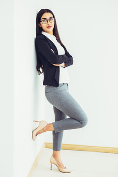 Full length portrait of content young pretty Indian business woman looking at camera, standing on one leg and leaning against wall with arms crossed. Isolated side view on white background.