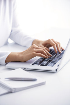 Typing on laptop keyboard. Close-up of a young woman holding brush in her hand and applying makeup. Isolated on light blue background.