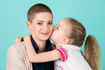 Young girl kissing mother, young cancer patient, on the cheek. Cancer and family support concept.