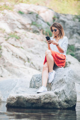 Young woman usin smartphone on the lake in the springtime