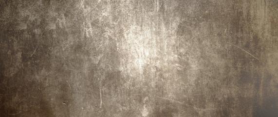 Textur einer dunklen und alten Betonwand als Hintergrund, auf die mittig Licht fällt