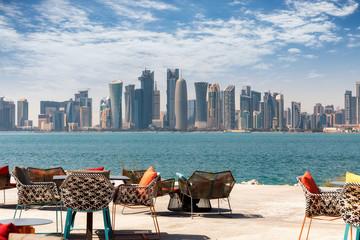 Stühle und Tische vor der Skyline von Doha, Katar, an einem sonnigen Tag
