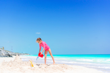 Adorable little girl playing with beach toys in shallow water