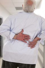 Overweight man with acute back ache bending over backwards to attenuate the pain, back view