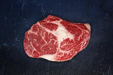 Rib eye steak on black slate