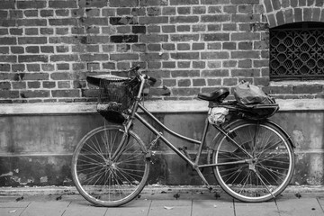 Photo sur Aluminium Black and white old style bicycle lay on brick wall