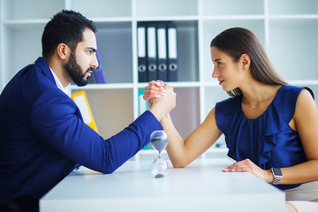 Side view portrait of man and woman armwrestling, exerting pressure on each other, looking eyes in eyes, struggling for leadership. Business, society concept photo