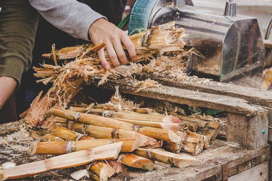 Man queezing sugar cane juice at street food market