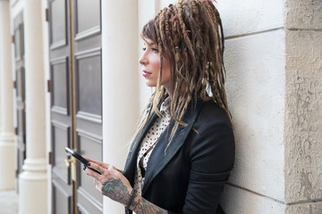 Beautiful woman with tattoos and dreadlocks texting on smart phone