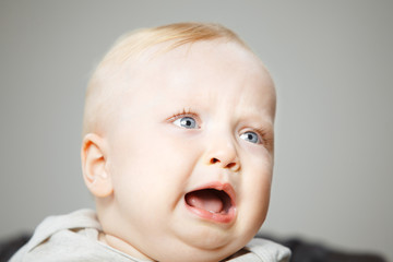 Disappointed blond baby boy cries hard portrait photo