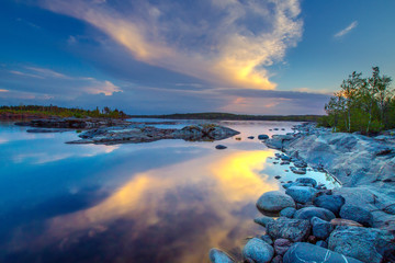 Wall Mural - Sunset. Beautiful clouds are reflected in the water of the lake. Ladoga lake. Nature of Karelia. Northern nature in the summer. Reflection in water. Karelia. Russia.