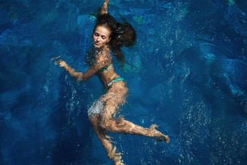 Girl, model elegantly swims in the pool. The image of life, style, fashion, beauty.