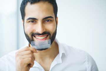 Teeth Whitening. Beautiful Smiling Man Holding Whitening Strip. High Resolution Image