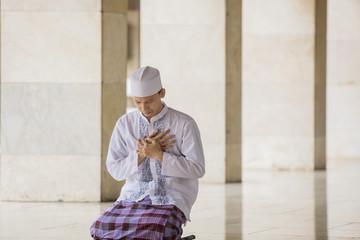 Sad Muslim man praying to the God