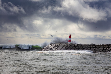 Stormy oceans with big waves crashing into a lighthouse