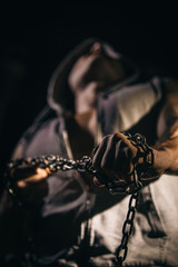 the hand of a man tearing the chain