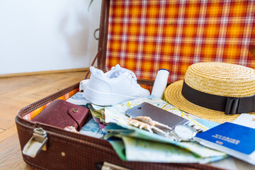 woman staff in suitcase. travel concept. camera laptop wallet hat on floor.