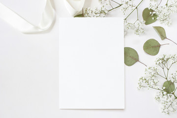 Styled stock photo. Feminine wedding desktop stationery mockup with blank greeting card, baby's breath Gypsophila flowers, dry green eucalyptus leaves, satin ribbon and white background. Empty space
