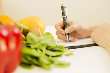 Nutritionist woman writing diet plan on table full of fruits and vegetables