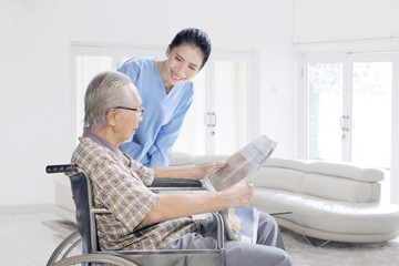 Female nurse talking with old man at home