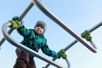 Child climbing metal bridge