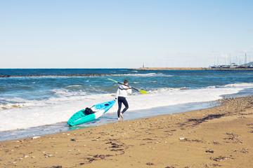 man carrying kayak at sea beach