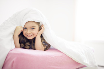 Portrait of a girl under covers by white sheet