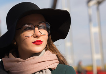 Lifestyle portrait of awesome young model posing at the bridge. Woman wearing fashionable hat, scarf and glasses