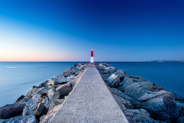 Evening landscape with a pier and a lighthouse in Empuriabrava, Spain