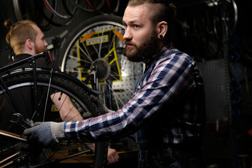Two handsome stylish male working with a bicycle in a repair shop. Workers repair and mounts bike in a workshop