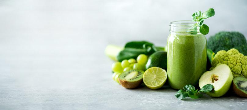 Glass jar mugs with green health smoothie, kale leaves, lime, apple, kiwi, grapes, banana, avocado, lettuce. Copy space. Raw, vegan, vegetarian, alkaline food concept. Banner