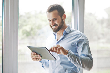 smiling businessman holding digital tablet touching with finger