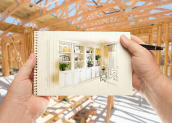 Hands Holding Pen and Pad of Paper with Built-in Shelves and Cabinets Inside House Construction Framing.