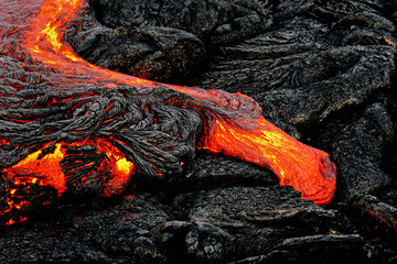 "Hot magma escapes from an earth column as part of an active lava flow, the glowing lava slowly cools and freezes - Location: Hawaii, Big Island, volcano ""Kilauea"""