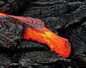 """Hot magma escapes from an earth column as part of an active lava flow, the glowing lava slowly cools and freezes - Location: Hawaii, Big Island, volcano """"Kilauea"""""""