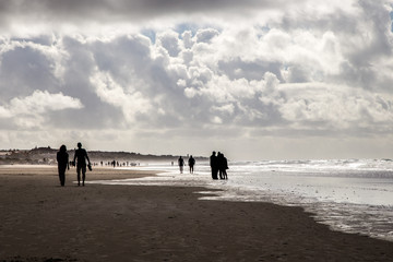 People in the beach under a beautiful cloudy sky