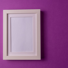 Mockup. Minimalism style. White empty picture frame against; abstract colored paper background; flat lay, copy space.