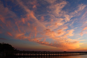 Golden and pink cloudscape at sunset over a wooden fishing pier jetty
