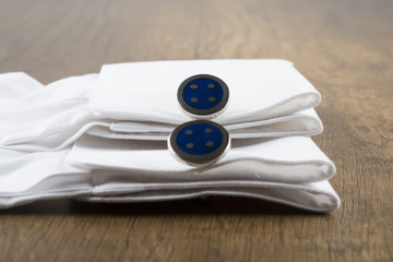 cufflinks with shirt on the wooden background. cufflink concept.
