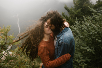 Couple Romantic Kissing on Top of A Windy Mountain Wind Blwon Hair