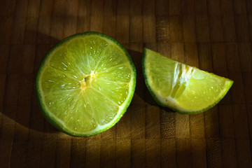 Sliced fresh juicy lime citrus on wooden cutting board isolated macro close up