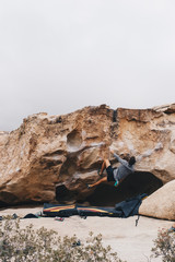 Man Bouldering outside with a heel hook