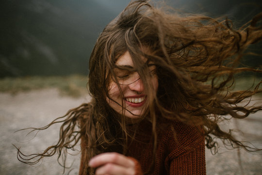 Woman Smiling With Wind Blowing Her Long Hair Around Her Face