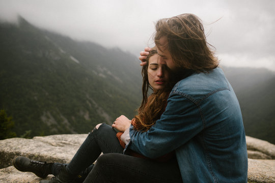 Couple in Love Sitting On Top of A Windy Mountain