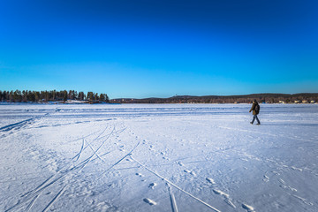 Falun - March 31, 2018: Traveler hiking on the frozen lake at Framby Udde near the town of Falun in Dalarna, Sweden