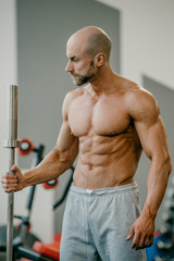 Shredded shirtless tough bodybuilder with beard posing with short barbell in a gym. Fit man trains.
