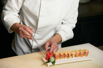 Male chef cooks preparing sushi in the restaurant kitchen. Chef cooking Classic Japanese sushi, served on a stone plate