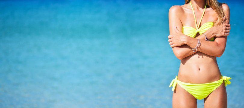 Wide summer banner with beautiful fit young woman in sexy yellow bikini at the beach. Girl in swimsuit and sunglasses, summer time near blue sea. Place for text