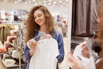 Positive curly young woman with delighted expression, makes shopping, holds white new blouse on hangers, reads information on label, stands in boutique with variety of clothes. Shopping centre