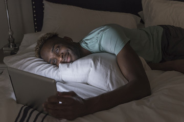 Young man using laptop, smiling and lying in bed at night